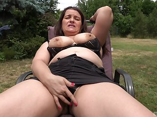Auntie shows off in the on every side yard, masturbating like a slut